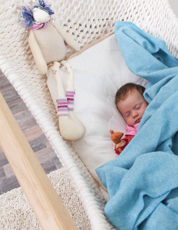 Ein Baby liegt im zur Babywiege umgebauten Traumschwinger XL