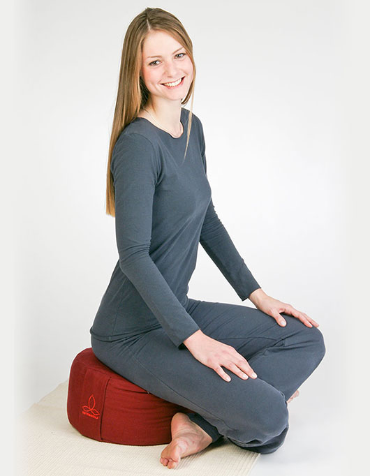 Im Schneidersitz auf Yogakissen sitzen