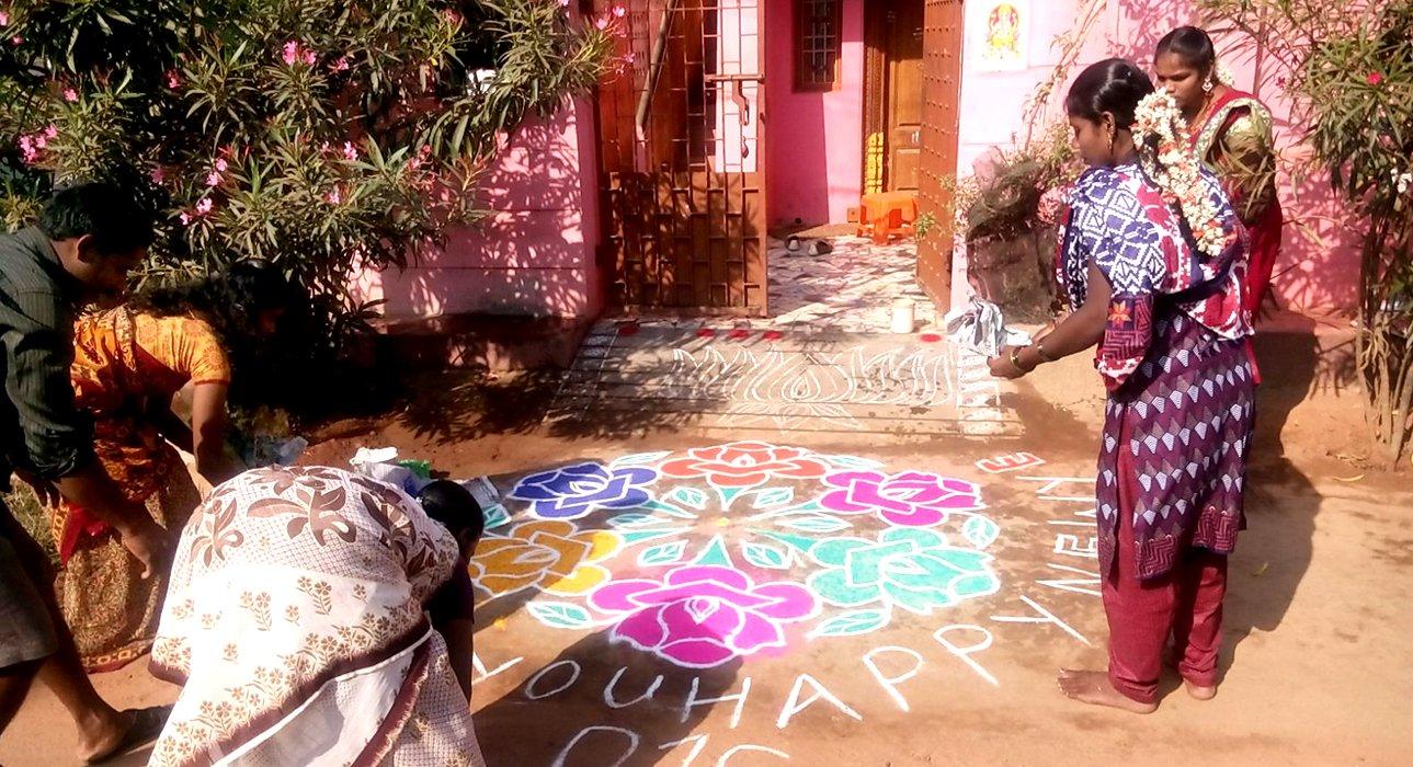 Indische Frauen malen Blüten auf den Boden